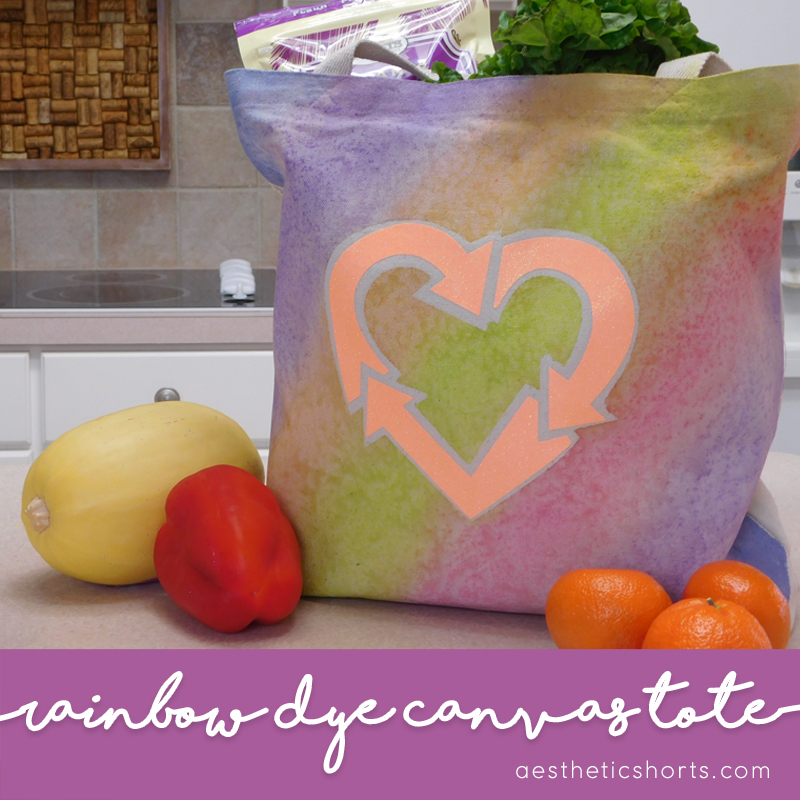 Rainbow Recycle Canvas Tote. This canvas tote is great to take with you to the grocery store, and the rainbow tie dye effect is simple to achieve using Dye-Na-Flow acrylic paint. The recycle symbol is from cut on the Silhouette Cameo from glitter heat transfer vinyl. The project can be done quickly and customized to your style.